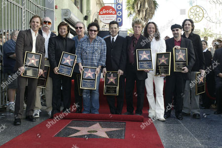 """CASTRONOVO Members of the band Journey pose after receiving a star on the Hollywood Walk of Fame, in Los Angeles. Band members are, from left, Jonathan Cain, George Tickner, former lead vocalist Steve Perry, Aynsley Dunbar, Neal Schon, Robert Fleischman, Ross Valory, Steve Augeri, Steve Smith and Deen Castronovo. Over a 30-year period, Journey released 18 albums, selling 50 million copies on the strength of radio hits such as """"Don't Stop Believin',"""" """"Who's Crying Now,"""" and """"Open Arms"""