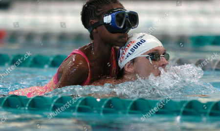 Stock Picture of KRAYZELBURG BROWN KING Olympic swimming gold medalist Lenny Krayzelburg helps Tyshell Brown-King swim a lap during a homecoming swimming event with children from Riverview Elementary School, in Baltimore