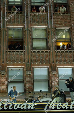 Trey Anastasio, left, Jon Fishman, center, and Mike Gordon of the rock band Phish perform on top of the Marquee of the Ed Sullivan Theater for the Late Show with David Letterman in New York, . Thousands of fans and pedestrians watched from the street as the band performed
