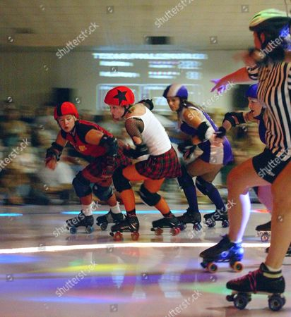 """MITE The official at right designates the lead jammer of the """"Hell Marys,"""" as she points toward Lane Greer, second from left with star on her helmet, during roller derby action, in Austin, Texas. Greer's teammate Heather Norwood, left, skates the pivot. They are followed by opposition teammates Amy Sherman and Heather Russell, partially obscured by the official, jammer, for the """"Hustlers"""