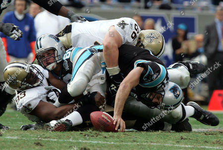 DELHOMME YOUNG HOWARD Carolina Panthers quarterback Jake Delhomme, center bottom, is sacked by New Orleans Saints' Brian Young, center top, and Darren Howard, left, during the first quarter, in Charlotte, N.C