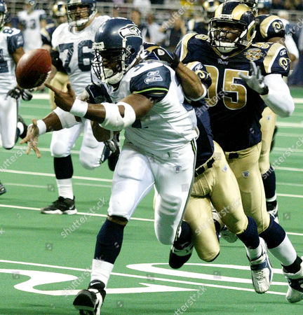 WILIAMS ALEXANDER HARGROVE St. Louis Rams' Aeneas Williams is sandwiched between Seattle Seahawks' Shaun Alexander, front, and Rams' Anthony Hargrove (95) as he strips the ball from Alexander in the fourth quarter in St. Louis . Williams recovered the fumble by Alexander to stop the Seahawks' scoring attempt. The Rams defeated the Seahawks 23-12