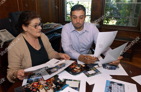 """Jennifer Hyman, left, and Hossein Alizadeh, of the Fellowship of Reconciliation, sort through photos that will be used in the organization's 'Iraq Photo Project', in Nyack, N.Y. More than 2,000 people bemoaning the war in Iraq, including teachers, lawyers and the father of a beheaded American, are sending pictures of themselves and their protest signs to Iraq to show civilians there """"what Americans are really like"""