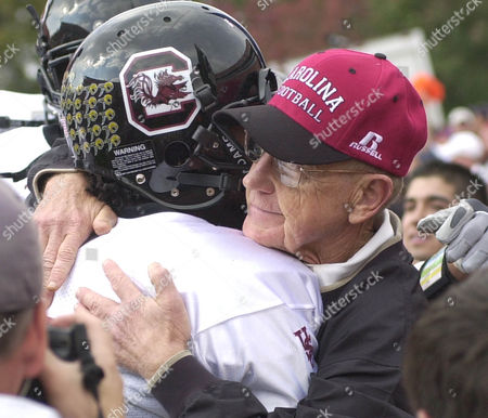 HOLTZ, GAUSE South Carolina coach Lou Holtz hugs Andrea Gause as he takes the field with his team against in-state rival Clemson, at Memorial Stadium in Clemson, S.C. Holtz has announced the he will step down as coach at South Carolina