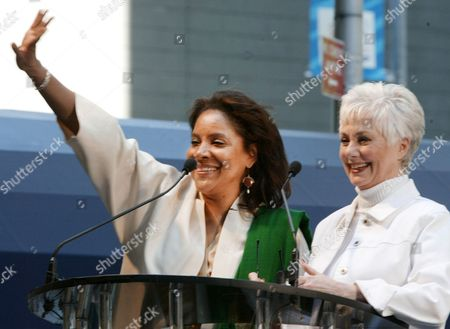 "Phylicia Rashad, left, of the Broadway play ""A Raisin in the Sun,"" waves to the crowd as Shirley Jones introduces her son and co-star of ""42nd Street,"" Patrick Cassidy, during ""Stars In The Alley,"" a free concert in New York's theater district, Wednesday, June 2. 2004. The program marks the end of the 2003-2004 theater season"