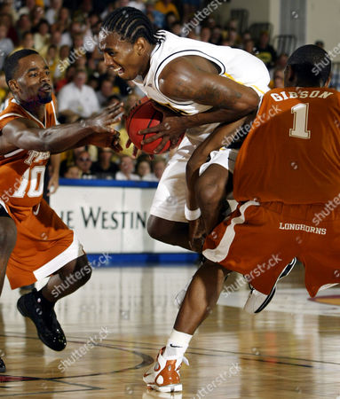 PIERCE TAYLOR GIBSON Iowa's Pierre Pierce, center, gets tripped up as he cuts between Texas' Kenny Taylor, left, and Daniel Gibson during the first half in the semifinals of the Maui Invitational in Lahaina, Hawaii