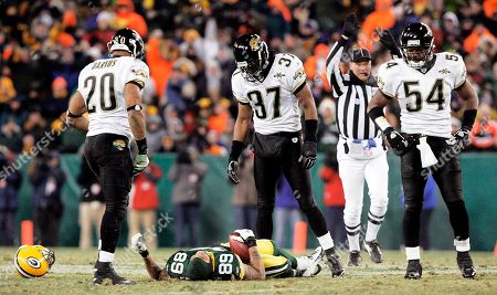 Stock Photo of Jacksonville Jaguars safety Donovin Darius (20), Deon Grant (37) and Mike Peterson (54) look down at Green Bay Packers receiver Robert Ferguson on the field in the fourth quarter, in Green Bay, Wis. Darius was ejected from the game after the hit. Ferguson left the field on a stretcher and was taken to a local hospital. The Jaguars won 28-25