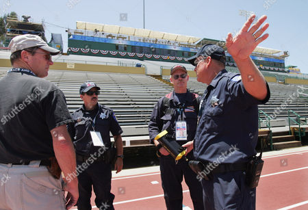 ERNST Sacramento firemen Rick Osborn, center, Paul Clark, second right and Michael Garner, right, confer with Mike Ernst, left, of the FBI before the start of the U.S. Olympic track & field trials in Sacramento, Calif., . Clark is holding a high tech sniffer used to detect chemicals, vapors and fumes