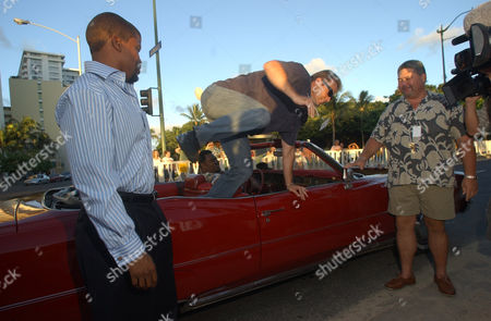 "ATKINS BELFOUR Sharif Atkins, left, watches Michael Biehn j jump out of a red Cadillac to arrive at the premiere of NBC's new police series ""Hawaii"" in Honolulu, Hawaii, . The show premiered on the sands of Waikiki Beach on a 30-foot screen.The vintage car is from the show"