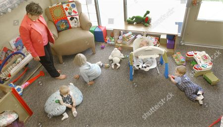 SPENCER Tracy Baroni Allmon, watches her four children, daughter, Piper, 3, in front of her, and her seven-month-old triplets, from left, Bailey, Luke, and Spencer, play at the Child Development Center at Bristol -Myers Squibb, where Allmon works, in Plainsboro, N.J