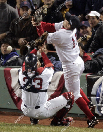 Boston Red Sox catcher Jason Varitek, left, and third baseman Bill Mueller collide as they chase, and lose, a foul ball from St, Louis Cardinals Jim Edmonds in the second inning of game two of the World Series in Boston