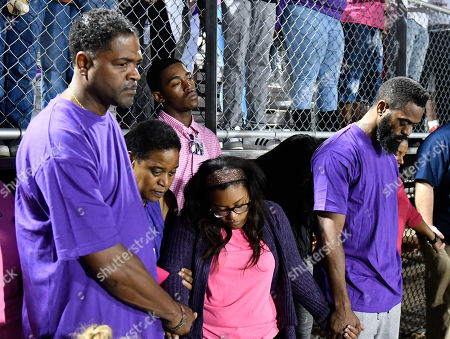 Tyson Gay, Shoshana Gay Tyson Gay, right, and Shoshana Boyd, second right, mother of Trinity Gay, hold hands during a moment of silence at a memorial service for their slain daughter at Lafayette High School, in Lexington, Ky. Several thousand people, turned out Monday night for a candlelight vigil in Kentucky to honor their 15-year-old daughter, who was fatally shot over the weekend