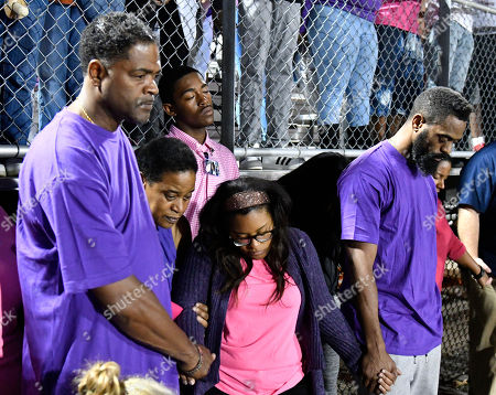 Stock Photo of Tyson Gay, Shoshana Gay Tyson Gay, right, and Shoshana Boyd, second right, mother of Trinity Gay, hold hands during a moment of silence at a memorial service for their slain daughter at Lafayette High School, in Lexington, Ky. Several thousand people, turned out Monday night for a candlelight vigil in Kentucky to honor their 15-year-old daughter, who was fatally shot over the weekend