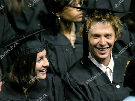 "AIKEN COACHMAN Pop star Clay Aiken, right, shares a laugh with friend Angela Coachman during commencement ceremonies at the University of North Carolina at Charlotte, . Aiken gained fame after his second-place finish in the hit television series ""American Idol."" He received his Bachelor of Arts in Special Education degree during the ceremony"