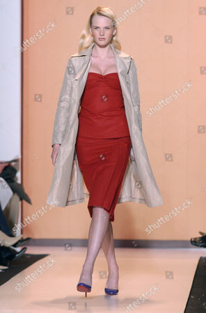 Model Anne V. wears a metallic khaki trench over a red wool twist camisole and red wool side-seamed skirt in the fall/winter 2004 collection of Chaiken, shown in New York
