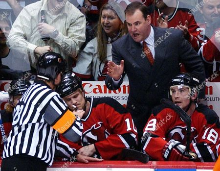 Stock Photo of BRYLIN New Jersey Devils coach Pat Burns talks to referee Brad Watson, left, during the second period of a first round NHL playoff game against the Philadelphia Flyers Monday night, in East Rutherford, N.J. Devils' Erik Rasmussen (10) and Sergei Brylin (18), of Russia are on the bench. The Devils won 4-2