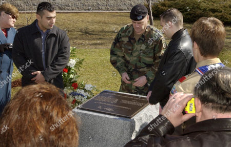 MILLEY Col. Mark Milley, center, unveils a memorial with crash survivors Spc. Edwin Mejia, left, and Spc. Dmitri Petrov, right, during a dedication ceremony in memory of 11 soldiers killed in a helicopter training accident last year at Fort Drum, N.Y