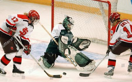 SIMARD FERGUSON GRILLS Dartmouth goalie Amy Ferguson, center, fends off St. Lawrence forward Sara Simard (17) and Chelsea Grills, right, during the first period to make a save during their third place game in the Women's Frozen Four NCAA Hockey tournament in Providence, R.I