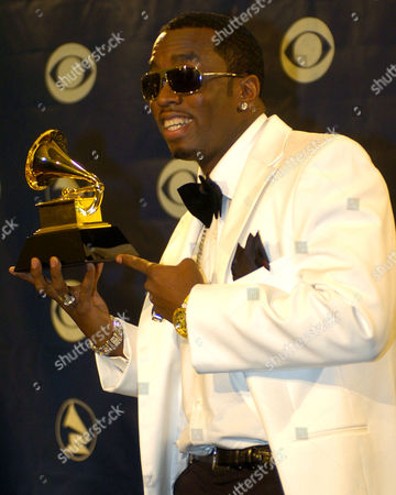 "Sean ""P. Diddy"" Combs points to his grammy backstage at the 46th Annual Grammy Awards in Los Angeles, Calif"