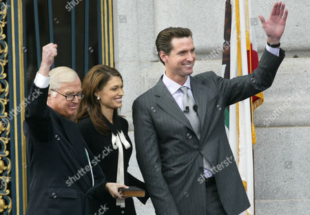 NEWSOM GUILFOYLE Newly sworn-in San Francisco Mayor Gavin Christopher Newsom, right, waves to supporters after taking the oath of office from his father, Judge William Newsom, left,, at City Hall in San Francisco. At center is Kimberly Guilfoyle Newsom, the mayor's wife