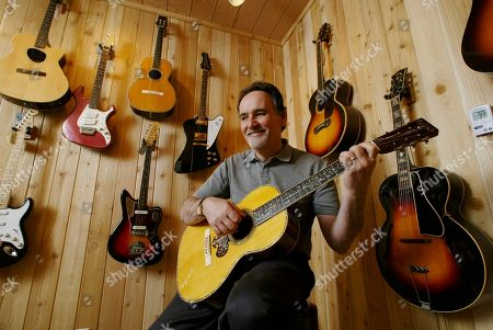 THOMAS Larry Thomas, chairman, co-chief executive officer and director of the Guitar Center Inc., plays a Martin classic guitar, at his office in Westlake Village, Calif. Guitar Center Inc., which is doing what none of its competitors have been able to do of late, expand its business by opening stores, including a new flagship store in Manhattan, all over the country