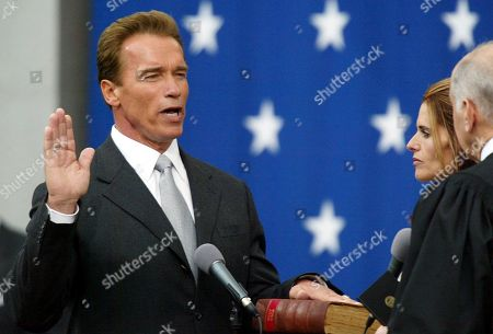 """Stock Picture of Arnold Schwarzenegger, Maria Shriver, Ronald George Arnold Schwarzenegger takes the oath of office for governor of California on the steps of the Capitol in Sacramento, Calif. Schwarzenegger's wife Maria Shriver stands to his side while California Supreme Court Chief Justice Ronald George administers the oath. In an interview with """"60 minutes"""" that is scheduled to air Sunday, Schwarzenegger says the affair he had with longtime housekeeper Mildred Baena, that led to a son, was """"the stupidest thing"""", he ever did to then-wife Maria Shriver"""
