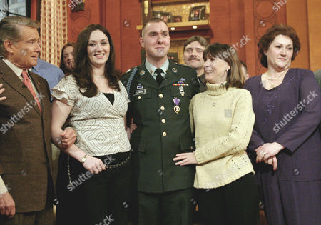 """The families of U.S. Army Specialist Robert Fleming, center, of Feds Creek, Ky., and his fianc April Zehr join host Regis Philbin, left, on the set of """"Live with Regis and Kelly"""" in New York, . Fleming was wounded by a roadside bomb four days before his tour in Iraq was to end. His wedding plans with Zehr were put on hold while he recuperated from extensive surgery. The two are scheduled to be married live on the air of """"Live with Regis and Kelly"""" on Friday, Feb. 6. From left are Philbin, Zehr, Fleming, Fleming's mother Annetta Fleming, and Zerh's mother Melissa Zehr. Flemings father, Joseph Fleming, is standing in the rear row between Joseph and Annetta"""