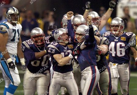 VINATIERI WILLIG Carolina Panthers Matt Willig, left rear, looks on as New England Patriots kicker Adam Vinatieri, center, is mobbed by his teammates after kicking a 41-yard field goal in the fourth quarter to beat the Panthers 32-29 in Super Bowl XXXVIII in Houston
