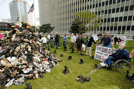 KOVIC Ron Kovic, a disable Vietnam War veteran, seen right in wheel chair, leads a prayer around a pile of shoes and combat boots laid out in regimental formation, representing the Iraqi civilians and U.S. soldiers killed since the start of the U.S.-led war in Iraq, Thursday, March, 18, 2004, at a demonstration marking the first anniversary of the war, at the Los Angeles Federal Building in Westwood, Calif