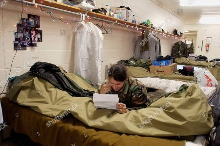 """HUBBARD After a day of training Sgt. Barbara J. Hubbard reads a letter from her oldest daughter in her barracks at Camp Atterbury near Edinburgh, Ind., . Sgt. Hubbard is a soldier in the 512th Engineer Battalion from the Ohio National Guard that oversees construction projects. The 512th are among the first of thousands of troops known as """"Operation Iraqi Freedom II fighters,"""" the next wave of troops to go to Iraq"""