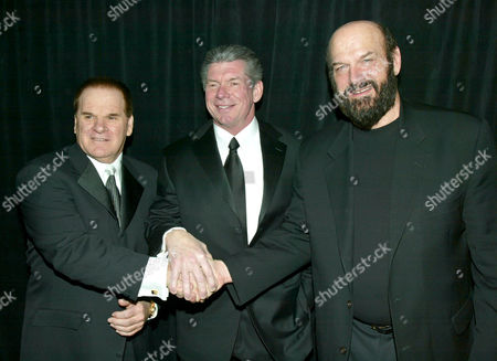 Baseball's Pete Rose, left, World Wrestling Entertainment chairman Vince McMahon, center, and Minnesota Governor Jesse Ventura put their hands together before Rose and Ventura were to be inducted into the WWE Hall of Fame, in New York