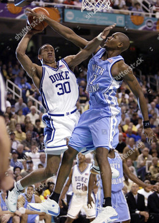 Duke's Dahntay Jones (30) fends off the defense of North Carolina's Jawad Williams during Duke's 75-63 win in the semifinal of the ACC tournament in Greensboro, N.C