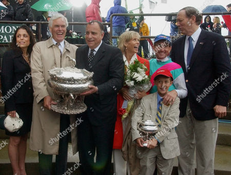 Stock Image of PATAKI Dr. John Chandler, second from left, of Juddmonte Farms, trainer Bobby Frankel, center, Suzze Bailey, winning jockey Jerry Bailey, and their son Justin, and New York Governor George E. Pataki celebrate in the winners' circle after Empire Maker won the Belmont Stakes at Belmont Park, in Elmont, N.Y. Woman at left is unidentified