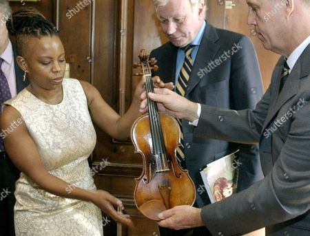 "ANGELINI Bruce Carlson, right, caretaker of the the legendary 260 year-old Guarneri violin, ""Il Cannone,"" hands the delicate instrument to jazz musician Regina Carter, left, at the Italian Cultural Institute in New York as the Institute;s Director Dr. Claudio Angelini looks on. Carter, who traveled to Genoa, Italy, in 2001, to play the 1743 instrument made by Guarneri del Gesu and owned by composer Niccolo Paganini, will play it again, Monday night at Lincoln Center's Alice Tully Hall. The last time the violin was played in America it received a three-minute ovation before being played"