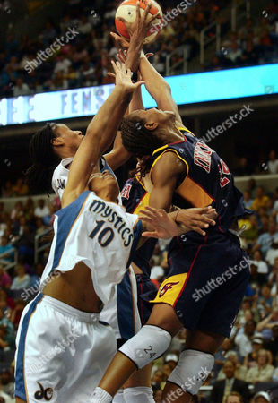 CATCHINGS PAGE HOLDSCLAW Indiana Fever's Tamika Catchings (24) leaps for a rebound against the Washington Mystics' Murriel Page (10) and Chamique Holdsclaw in second half WNBA action at the MCI Center in Washington, . The Fever won in overtime, 92-91
