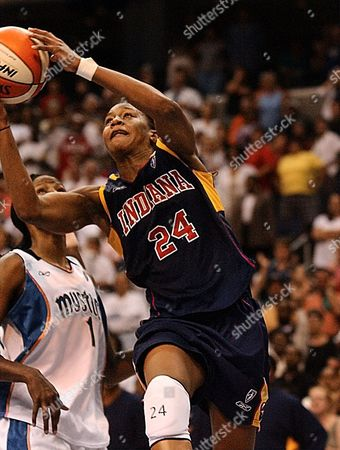 CATCHINGS HOLDSCLAW Indiana Fever's Tamika Catchings (24) lays up the game-winning basket at the buzzer in overtime against the Washington at the MCI Center in Washington, . At left is Mystics Chamique Holdsclaw (1). The Fever won 92-91