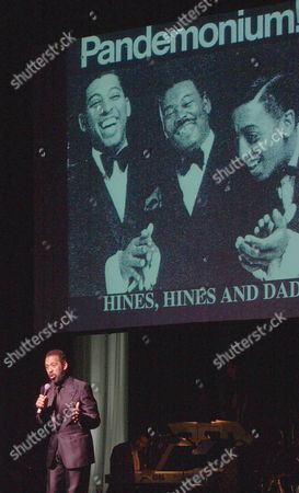 Maurice Hines Jr. speaks in front of a picture showing himself, left, his father Maurice Hines Sr., center and the late Gregory Hines, right, during a memeorial celebration honoring the artistic legacy of Gregory Hines at New York's Apollo Theater. Gregory Hines died at age 57 in July