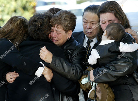 LAU Ruth Lau, center, is consolded by family and friends as her husband Augustine, rear, looks, during funeral services for their daughter, Army Pfc. Karina Lau, outside of St. Jude Thaddeus Catholic Church in Livingston, Calif., on . At right is the Laus' daughter in-law Mary Lau, holding one year-old son Anthony. Lau died Nov. 2, along with 15 other U.S. soldiers, when their helicopter was shot down over Iraq