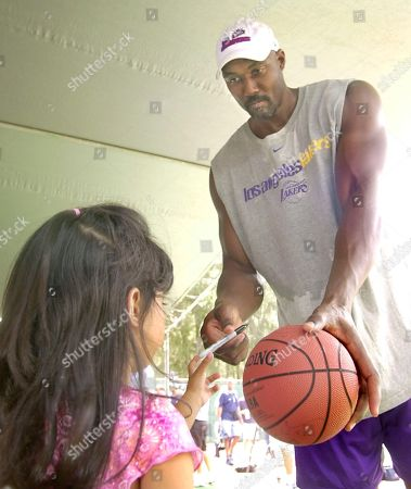 MALONE PHILLIPS Los Angeles Lakers forward Karl Malone signs an autograph for five-year-old Abby Phillips, at Bellows Air Force Station north of Honolulu, Hawaii. The team went to the military station to play games of paint ball and meet members of the armed services who recently served in Afganistan and Iraq and their families
