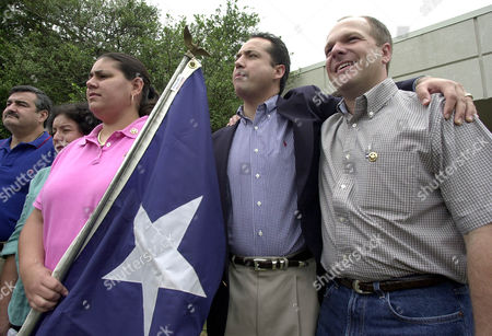 CANALES MENENDEZ HOMER Texas State Rep. Gabi Canales, D-Alice, left, holds a Texas flag as Rep. Jose Menendez, D-San Antonio, center, and Rep. Mark Homer, D-Paris, right, stand arm in arm during a news conference at a hotel in Ardmore, Okla., . Rebellious Democrats who fled the state Capitol spent a second day in Oklahoma on Tuesday and criticized U.S. House Majority Leader Tom DeLay for pushing the GOP drive in Texas to redraw the state's congressional districts