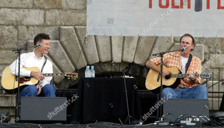 """HIATT Lyle Lovett, left, smiles as he listens to fellow singer-songwriter John Hiatt sing """"The Tiki Bar Is Open,"""" as they shared the stage during the Apple & Eve Newport Folk Festival in Newport, R.I., . Hiatt and Lovett were joined on stage by Joe Ely and Guy Clark for the all acoustic set"""
