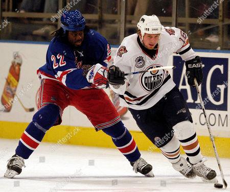 New York Rangers' Anson Carter chases after Edmonton Oilers Mike York during the first period at Madison Square Garden in New York