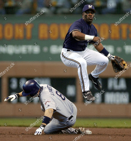 YOUNG LORETTA Milwaukee Brewers' second baseman Eric Young leaps over San Diego Padres' Mark Loretta to complete a double play on a ball hit by Lou Merloni in the sixth inning, in Milwaukee