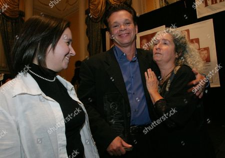 Singer, songwriter and musician John Mellencamp, center, shares a warm moment with Nora Guthrie, right, and Anna Canoni, as they pose for a photograph at the Huntington's Disease Society of America's seventh annual Guthrie Awards dinner in New York. Mellencamp was presented with the Woody Guthrie Award at the dinner for his embodiment of Woody Guthrie's ideals. Nora Guthrie is the daughter and Anna Canoni is the granddaughter of Woody and Marjorie Guthrie