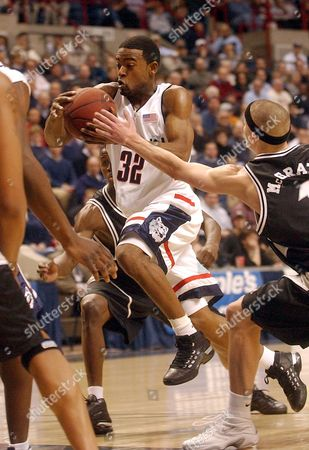 Stock Image of ROBERTSON MCGRATH Connecticut's Tony Robertson drives for the basket as Providence's Donnie McGrath reaches to try to stop him in the first half at Storrs, Conn