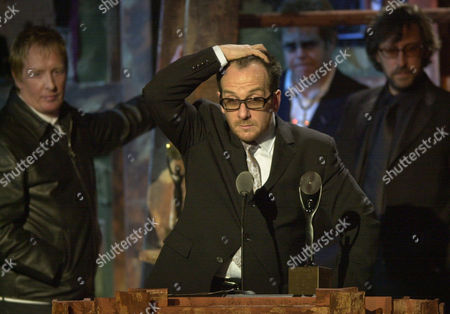 Elvis Costello reacts as fellow band members Bruce Thomas, bass player, left, and keyboardist Steve Nieve right, look on during the 18th Annual Rock and Roll Hall of Fame induction ceremony, at New York's Waldorf Astoria. Elton John looks on in center