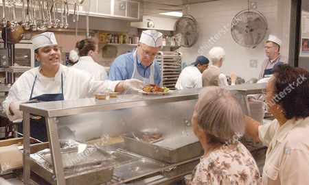 GARCIA SWIFT Liz Garcia, left, a culinary student, and Bill Swift, center, serve lunch, which costs a dollar, at the city-subsidized Encore Senior Center at St. Malachy's Catholic Church in New York. Frugality is the watchword for many of the nation's elderly who survive on fixed incomes