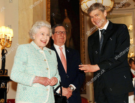 Stock Image of Queen Elizabeth II meeting Arsenal chairman Peter Hill-Wood and manager Arsene Wenger (right). The Queen finally met Arsenal team members for tea - four months after she was forced to take time out due to injury. The 80-year-old monarch cancelled a trip to see the club's new Emirates Stadium in October after suffering from a bad back.