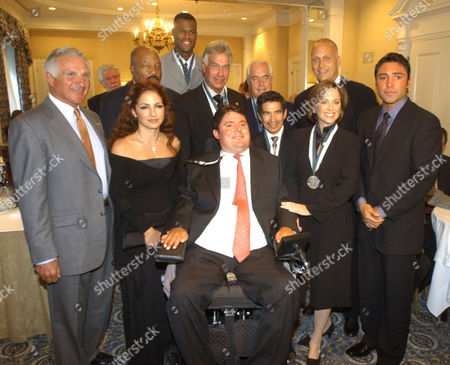 Marc Buoniconti, center, paralyzed from a college football game, is joined by his farthe Nick Buoniconti, far left, and celebrities for the 18th Annual Great Sports Legends Dinner in New York, . Gloria Estefan, second from left, Jim Brown, third from left, David Robinson, fourth from left, Bruce Fleisher, fifth from left, Roger Penske, fifth from right, Laffit Pincay, fourth from right, Cal Ripken, Jr., third from right, Dorothy Hamill, second from right and Oscar De La Hoya, farright, are among this year's honorees at the fundraiser event to raise awareness for spinal cord injury and the Buoniconti Fund to Cure Paralysis