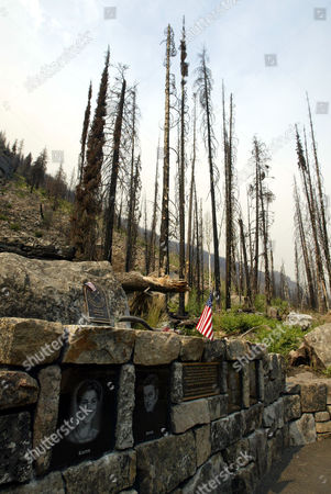 Smoke from the Farewell Creek Fire rises in the sky, near Winthrop, Wash., above a memorial which marks the location where four firefighters died on July 10, 2001 while fighting the Thirtymile Fire. The Farewell Creek Fire, which has involved 48,000 acres so far, reburned several hundred acres of the Thirtymile Fire area. The memorial bears the photographs and names of Karen Fitzpatrick, Devin Weaver, Tom Craven, and Jessica Johnson